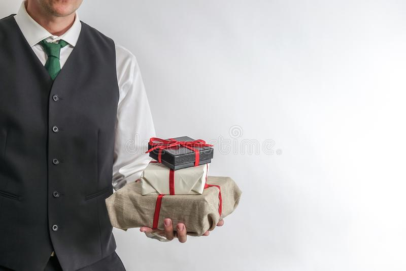 拿着圣诞节礼物盒/礼物的衣服背心的人 免版税库存图片