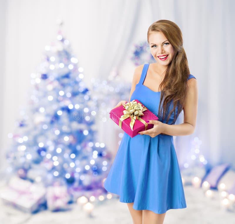 拿着圣诞节礼物礼物盒,式样女孩,蓝色树的妇女 免版税库存图片