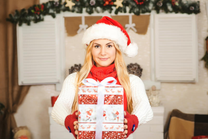 拿着圣诞节礼物箱子的愉快的少妇金发碧眼的女人 免版税库存照片