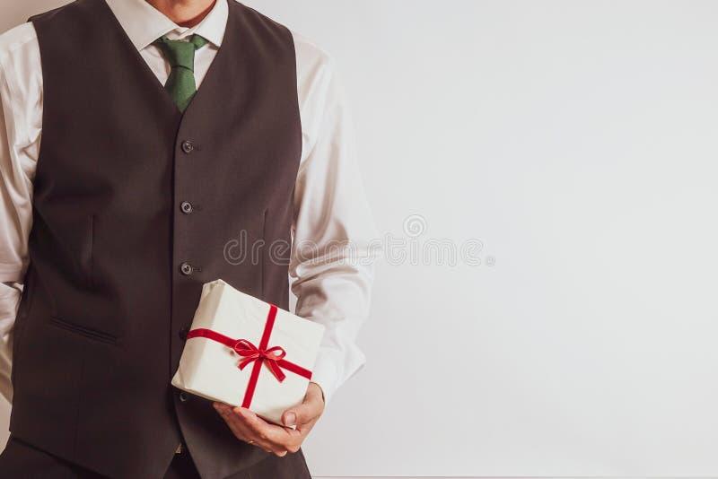 拿着圣诞节礼物/礼物的衣服背心的人 免版税库存图片