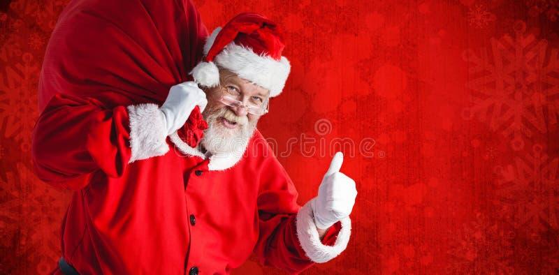 拿着圣诞节袋子的圣诞老人画象的综合图象,当打手势时 库存照片