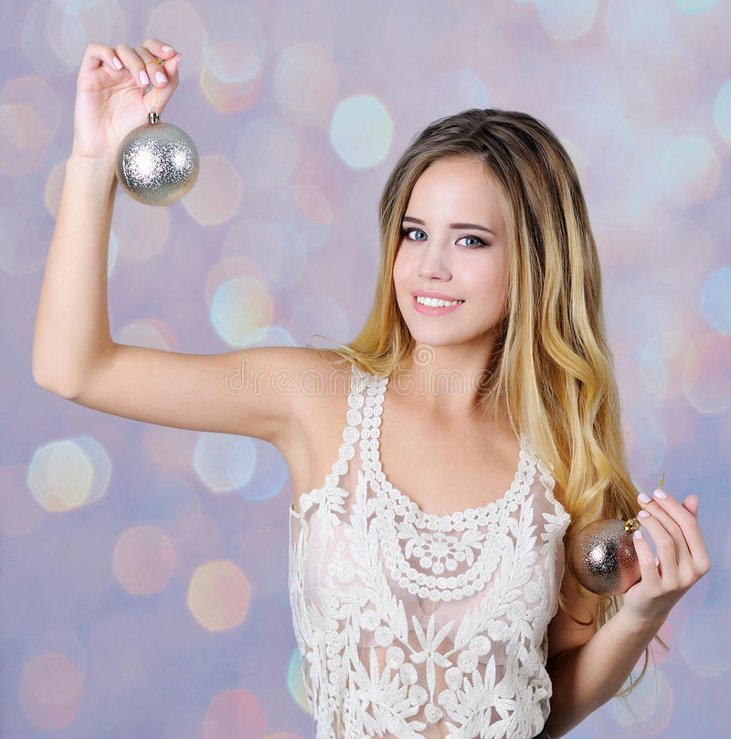 拿着圣诞节装饰品的美丽的女孩 库存图片