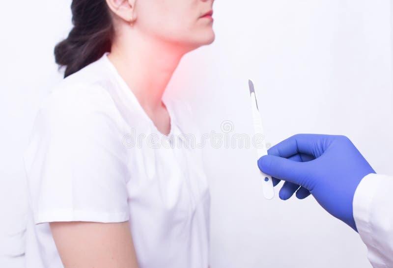 拿着在一个女孩的背景的医生一把外科解剖刀以喉头疾病,去除增殖腺的概念  免版税库存照片