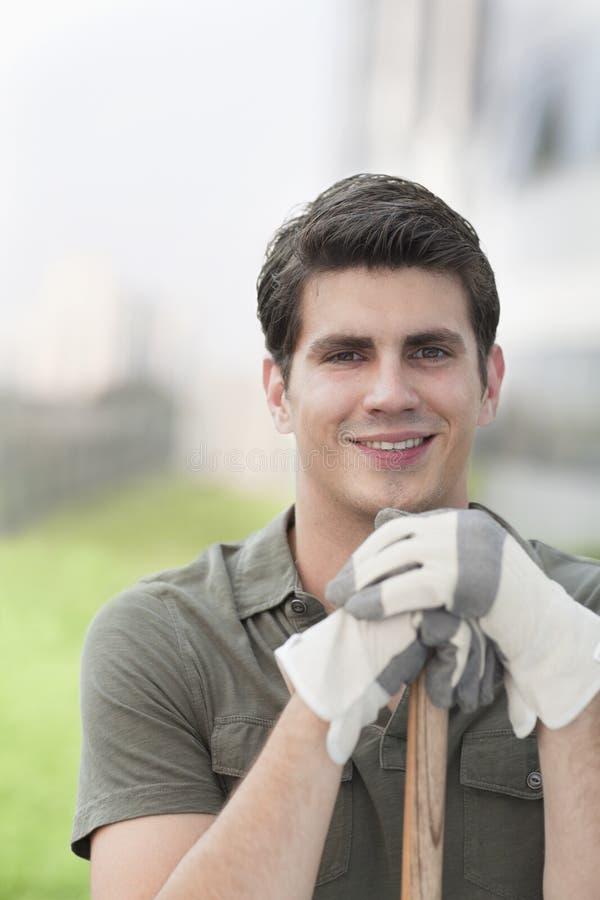 拿着在一个屋顶上面庭院的年轻微笑的人画象一把犁耙在城市 库存照片