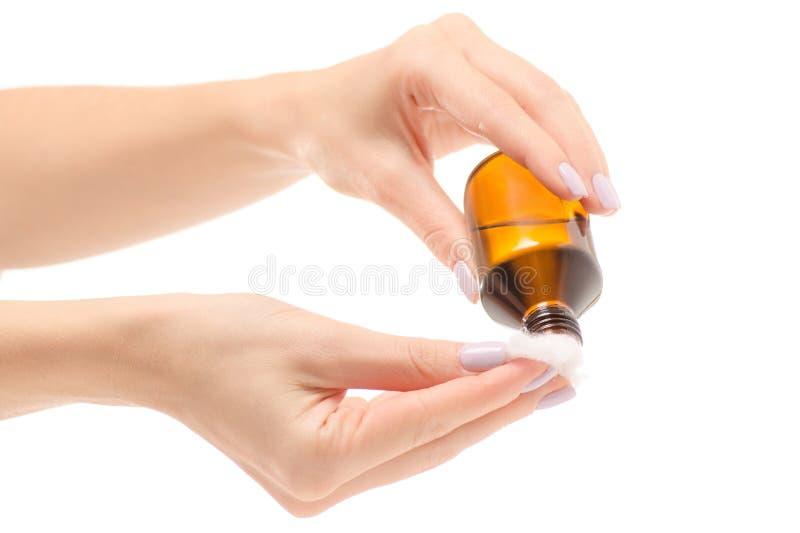 拿着在一个玻璃瓶子的女性手过氧化物棉绒棉绒 免版税库存照片