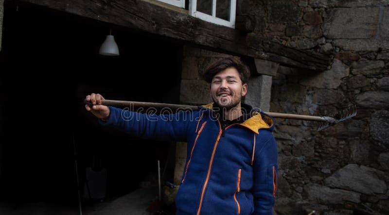拿着在一个石房子前面的微笑的年轻人一把犁耙a的 库存照片