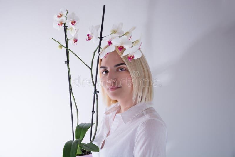 拿着在一个罐的年轻女人一朵兰花花在白色背景在演播室 免版税库存图片