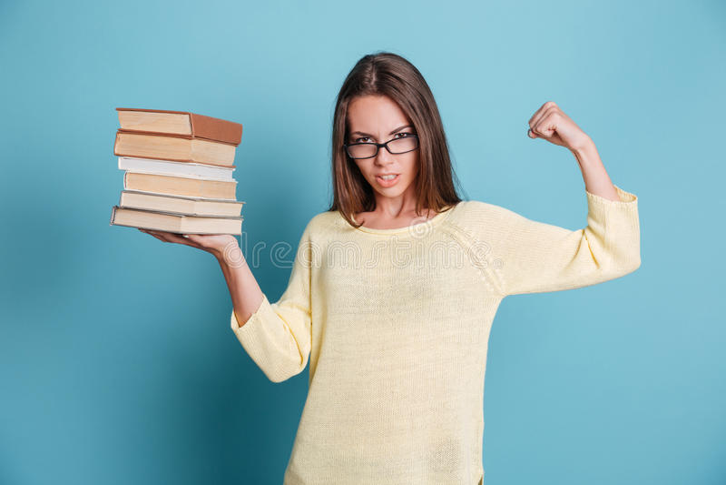 拿着在一只手佩带的镜片的坚强的聪明的女孩书 图库摄影