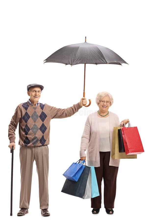 拿着在一名年长妇女的年长绅士一把伞与 免版税库存照片