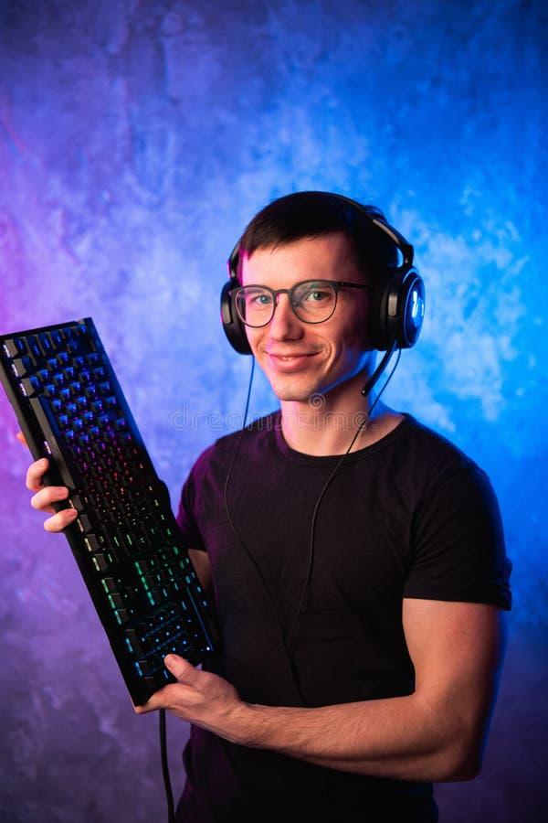 拿着在五颜六色的桃红色和蓝色霓虹灯墙壁的专业男孩游戏玩家赌博键盘 赌博游戏玩家概念 免版税图库摄影