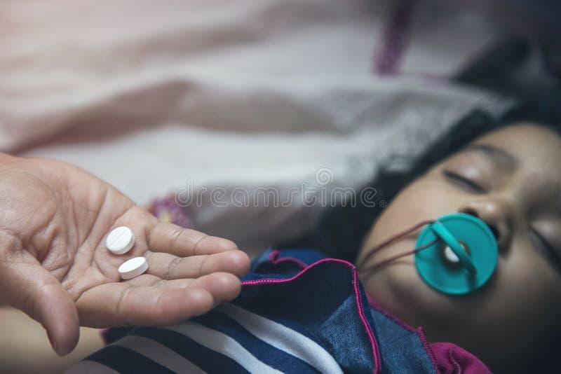 拿着在亚洲孩子的手医学药片与在她的嘴的安慰者 免版税库存照片
