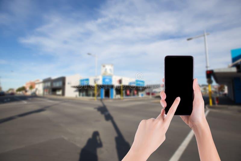 拿着在交叉点背景的妇女手智能手机 免版税库存图片