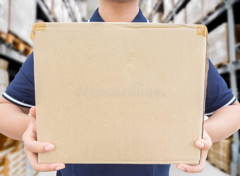 拿着在仓库被弄脏的背景的蓝色制服的送货人箱子 免版税库存图片