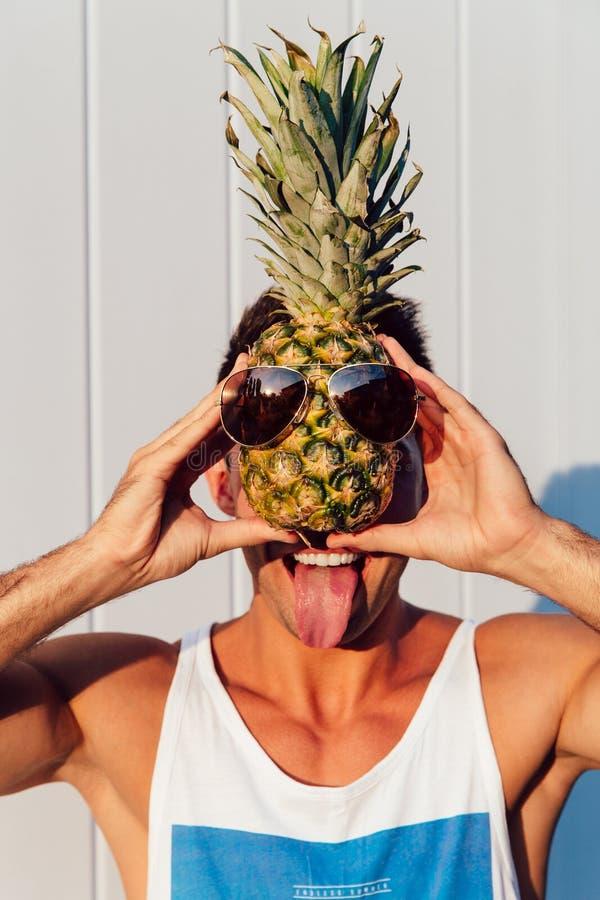 拿着在他的面孔前面的一个菠萝和显示舌头的滑稽的人 库存照片