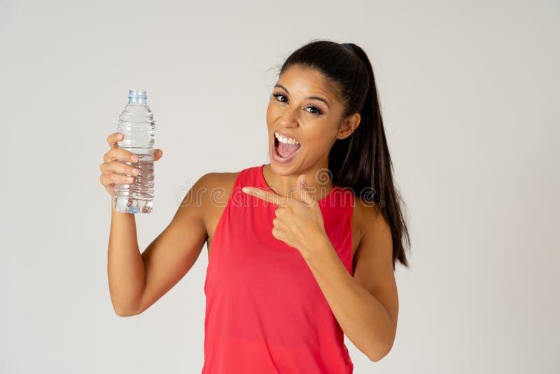 拿着在健康生活方式概念的健康可爱的体育妇女水瓶 免版税库存照片