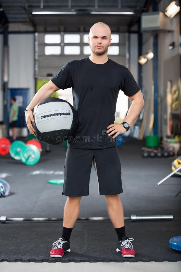 拿着在健身俱乐部的坚定的男性运动员药丸 免版税库存照片