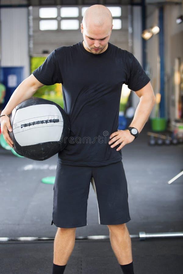 拿着在健身俱乐部的坚强的男性运动员药丸 库存图片