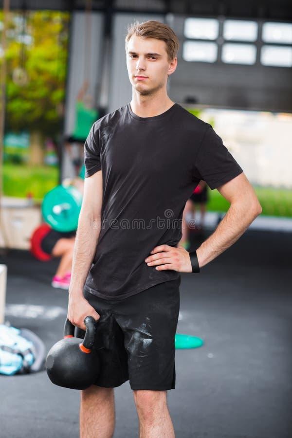 拿着在健身俱乐部的确信的体育教师kettlebell 库存图片