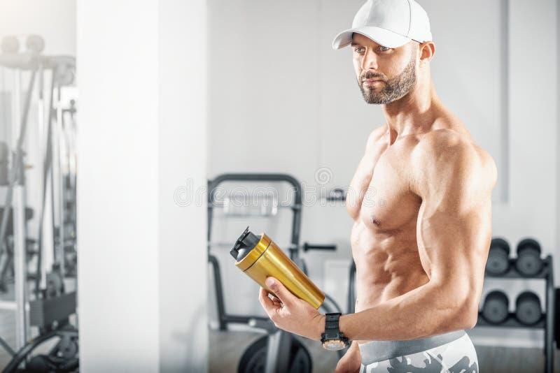 拿着在健身房的Fti人蛋白质振动器 免版税库存照片