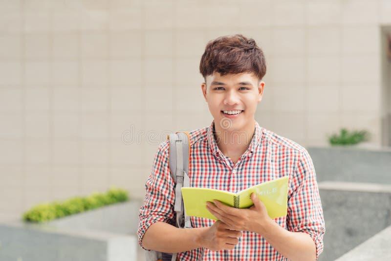 拿着在公园的学院亚裔男学生书 库存图片
