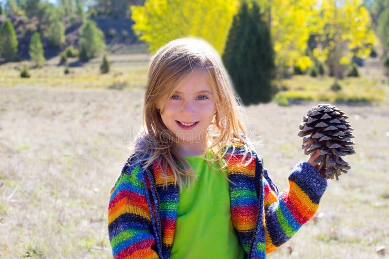 拿着在冬天秋天的儿童小女孩杉木锥体 图库摄影