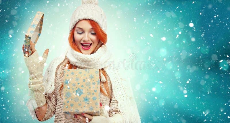 拿着在冬天背景的购物妇女礼物盒与雪在黑星期五,圣诞节和新年假日 销售额 库存图片