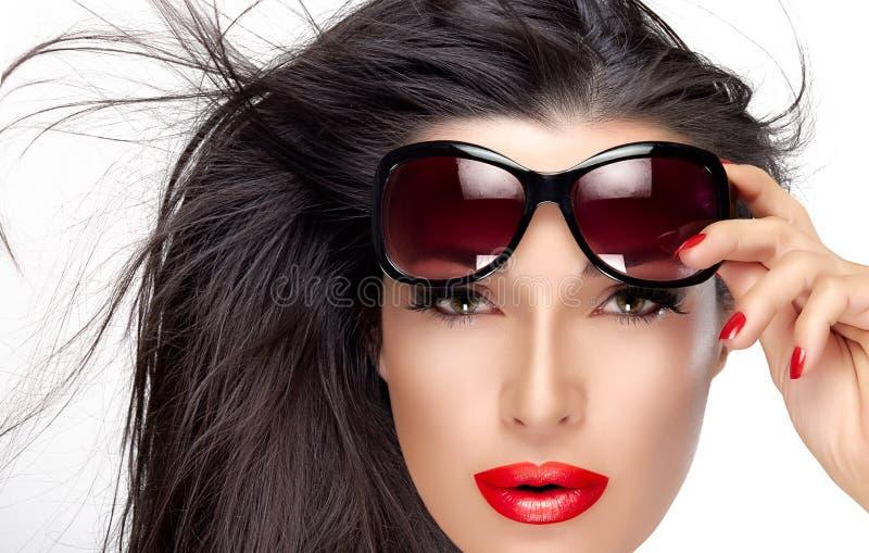 拿着在前额的美好的模型时尚太阳镜 免版税库存照片