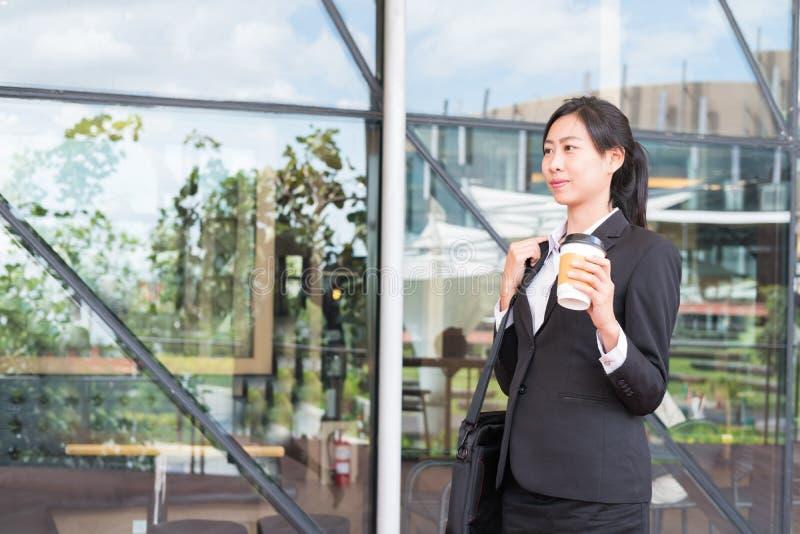 拿着在办公楼之外的愉快的女实业家咖啡 豆杆 库存照片