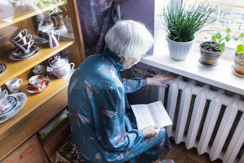 拿着在加热的幅射器前面的妇女现金 加热的付款在冬天 选择聚焦 图库摄影