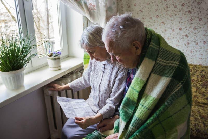 拿着在加热的幅射器前面的妇女现金 加热的付款在冬天 选择聚焦 库存照片