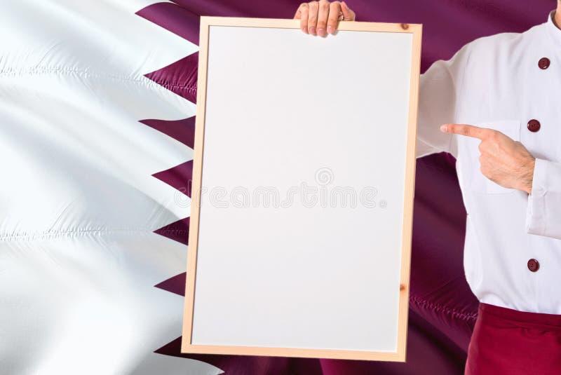 拿着在卡塔尔旗子背景的Qatari厨师空白的whiteboard菜单 烹调指向文本的佩带的制服空间 库存图片