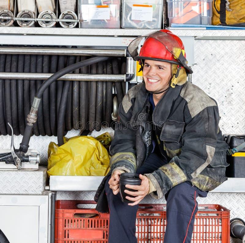 拿着在卡车的愉快的消防员咖啡杯在消防局 库存图片