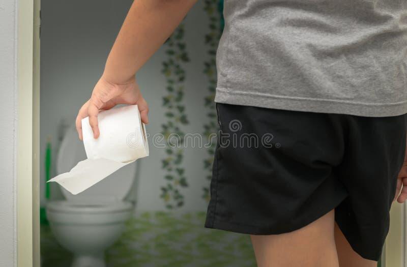 拿着在卫生间前面的男孩卫生纸卷 图库摄影