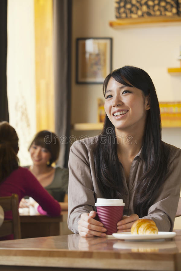 拿着在咖啡店的美丽的少妇咖啡杯,北京 免版税库存图片