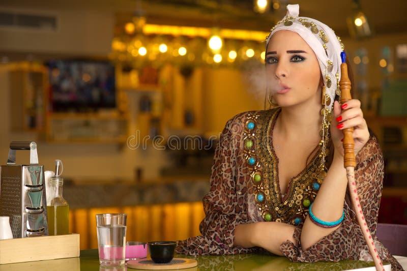 拿着在咖啡店的阿拉伯女孩水烟筒管子 免版税库存照片