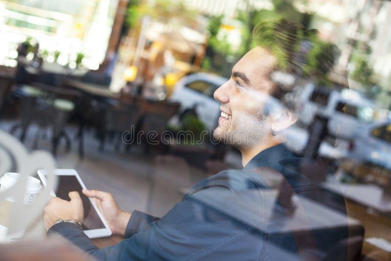 拿着在咖啡馆的年轻人数字式片剂 库存照片