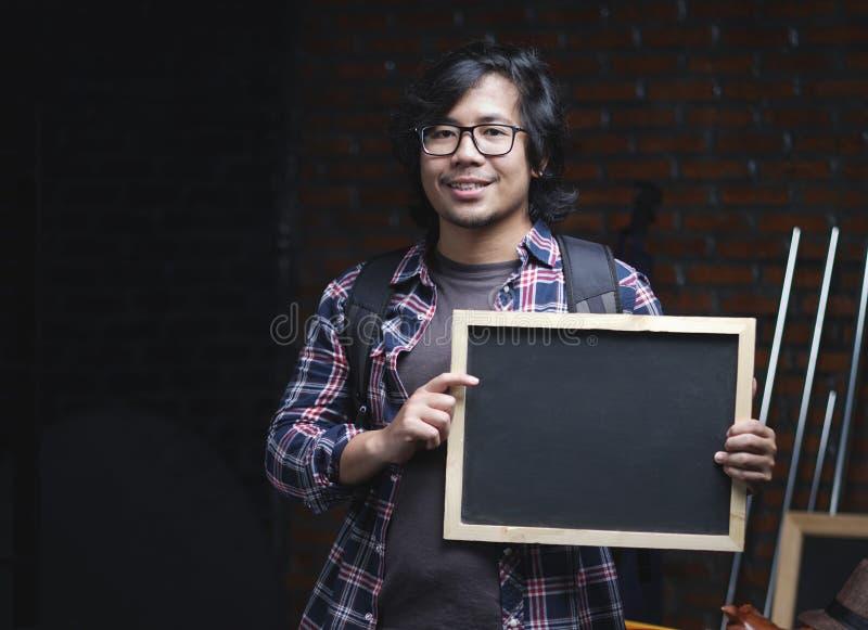 拿着在商品里面的亚裔大学生画象黑板 库存照片