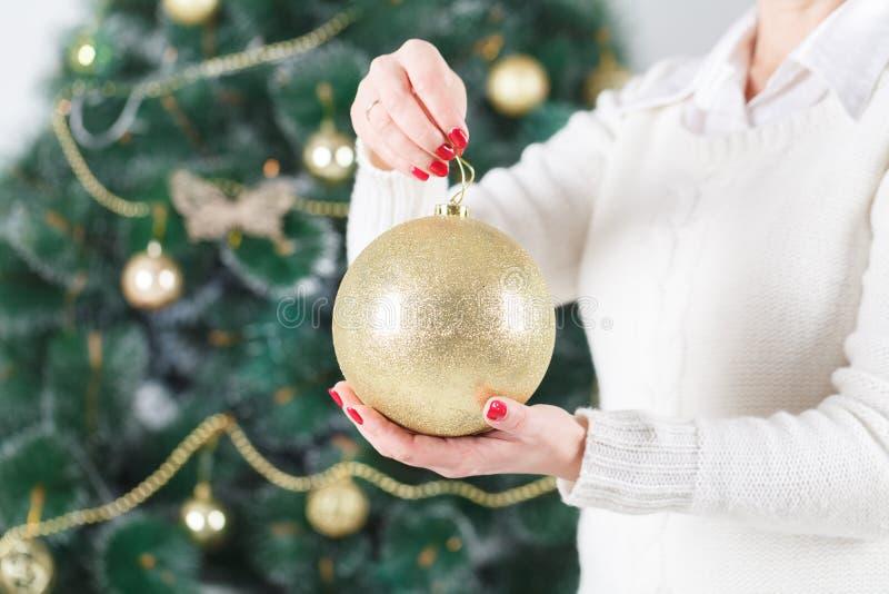 拿着在圣诞树前面的愉快的少妇圣诞节球 库存照片