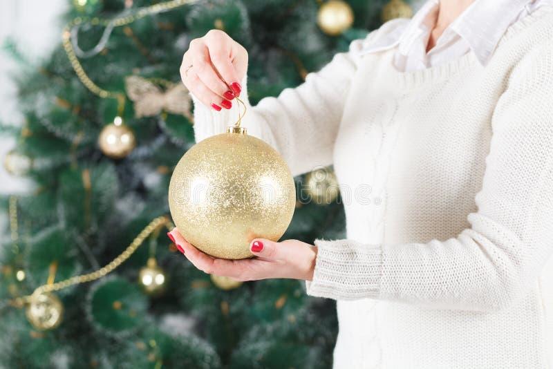 拿着在圣诞树前面的愉快的少妇圣诞节球 图库摄影