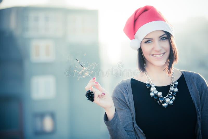 拿着在城市背景的孟加拉光愉快的妇女的画象  有闪烁发光物的圣诞节妇女 微笑的brune画象  免版税图库摄影