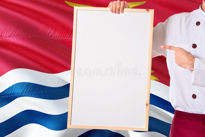 拿着在基里巴斯旗子背景的厨师空白的whiteboard菜单 烹调指向文本的佩带的制服空间 免版税库存照片