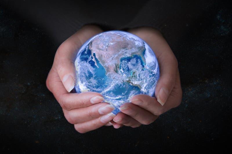 拿着在外层空间,概念救球的女性手地球worl 免版税图库摄影