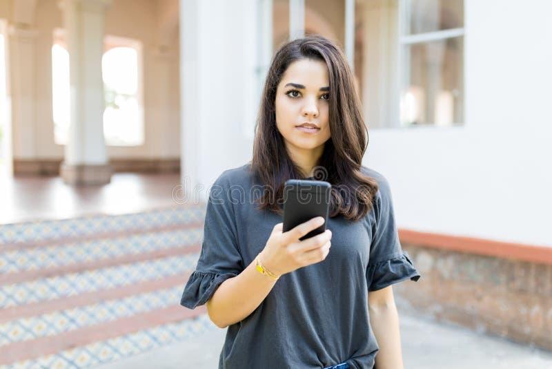 拿着在大厦之外的女性博客作者手机 免版税库存图片