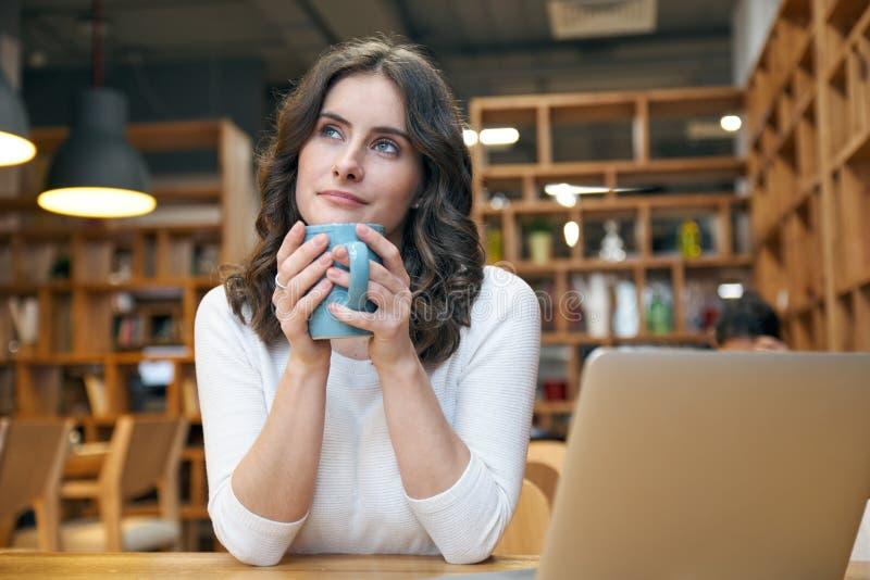 拿着在她前面的美丽的少妇女孩杯子用看坐直桌的两只手和渴望的梦想的表示 库存照片
