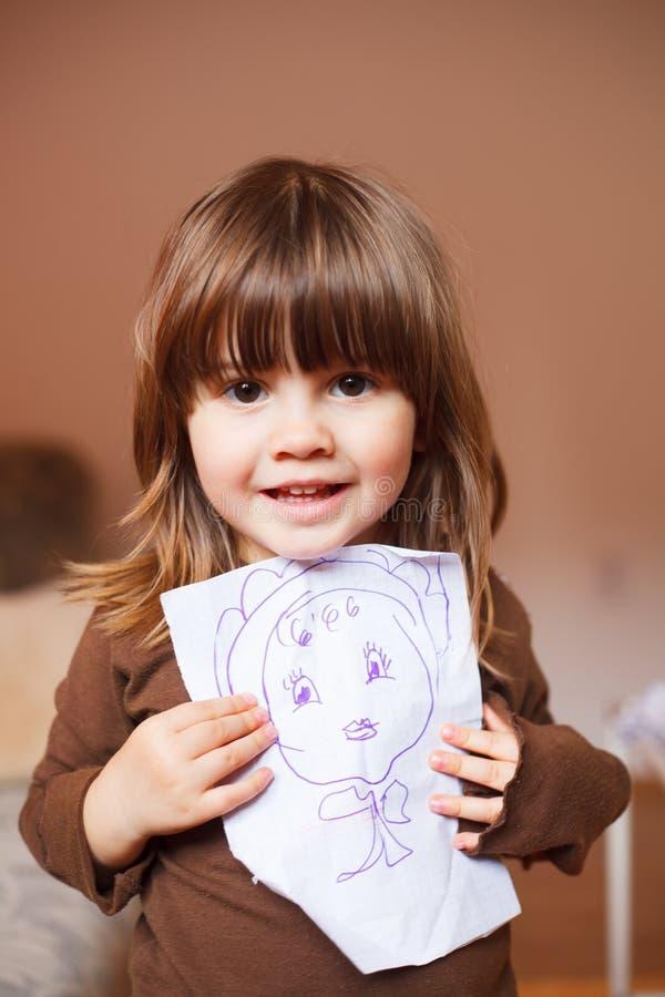 拿着在她前面的逗人喜爱的小女孩一张图画 库存照片