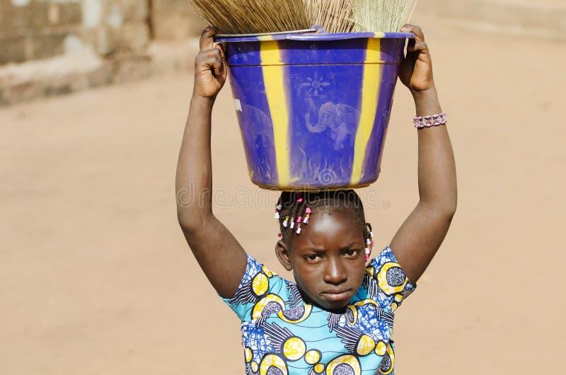 拿着在她坚硬的Wom的一点非洲种族学校女孩水槽 库存照片