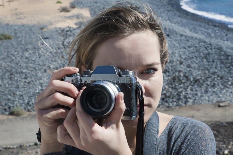 拿着在她的右眼睛的白种人种族的年轻千福年的女性一台数字式,专业照相机 免版税图库摄影