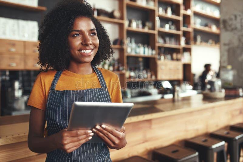 拿着在她的咖啡馆的年轻女性所有者数字片剂看aw 库存照片