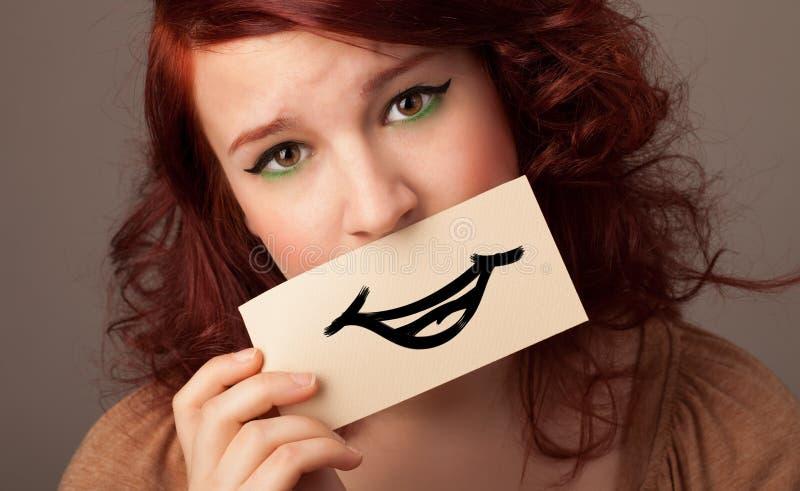 拿着在她的嘴前面卡片的人 免版税库存图片