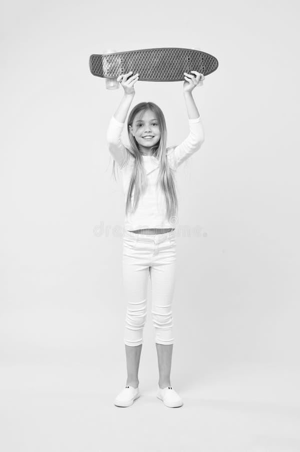 拿着在她的头上的女孩紫罗兰色滑板 街道种族的,愉快的童年概念冠军 在白色套头衫的孩子 免版税库存照片